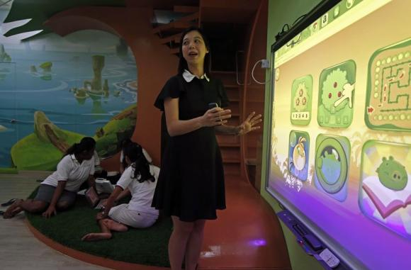 Dreamkids Kindergarten principal Choy shows how the Smart Board is used for educational games in class as teachers plan their lessons in an Angry Birds-inspired classroom environment in Singapore